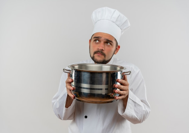 鍋を保持し、白いスペースに孤立して見上げるシェフの制服を着た思いやりのある若い男性料理人