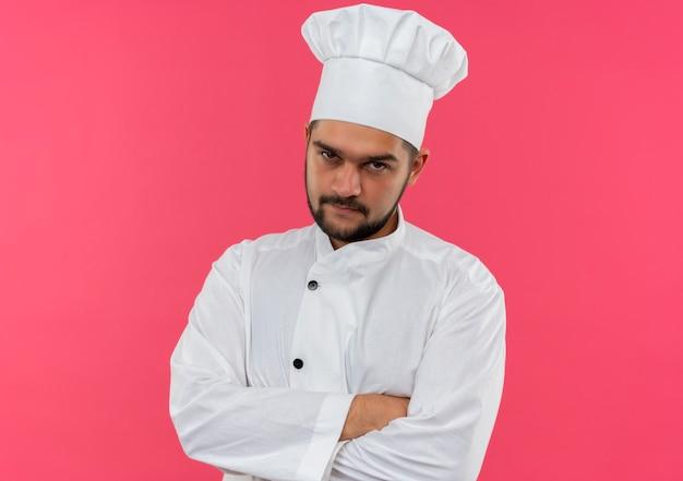 ピンクの空間に孤立して見える閉じた姿勢で立っているシェフの制服を着た思いやりのある若い男性料理人