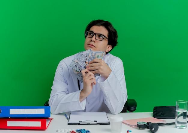 녹색 벽에 고립 된 측면을보고 돈을 들고 의료 도구와 책상에 앉아 안경 의료 가운과 청진기를 착용하는 사려 깊은 젊은 남성 의사