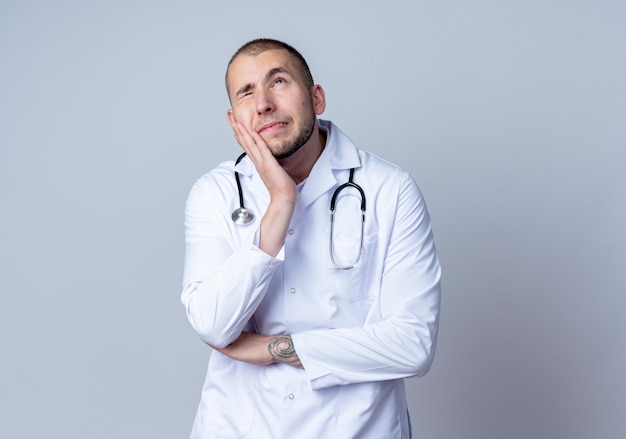 Thoughtful young male doctor wearing medical robe and stethoscope around his neck putting hand on cheek looking up with one eye closed isolated on white wall