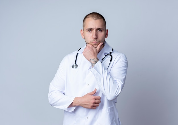 Thoughtful young male doctor wearing medical robe and stethoscope around his neck putting hand on chin isolated on white wall