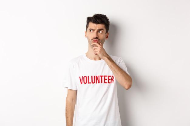 Вдумчивый молодой мужчина-доброволец в белых футболках ищет решения, смотрит в левый верхний угол и думает, стоя над студией.