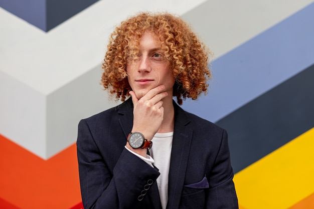 Thoughtful young male with curly ginger hair in elegant suit touching chin and looking away while standing near geometric wall on city street
