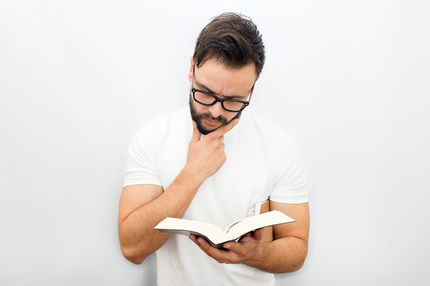 Thoughtful young man in glasses standing and reading book. he holds it in left hand. another one in under chin.