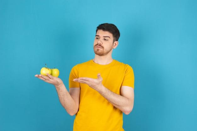 Заботливый молодой человек держит свежие органические яблоки и смотрит на него.