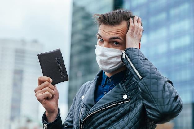 보호 마스크에 사려 깊은 젊은이 그의 여권을 보유하고 있습니다. 복사 공간 사진
