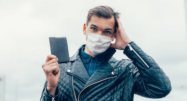 보호 마스크에 사려 깊은 젊은 남자가 그의 여권을 보유