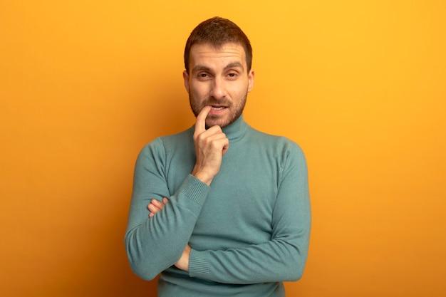 Giovane premuroso guardando il dito mordace anteriore isolato sulla parete arancione