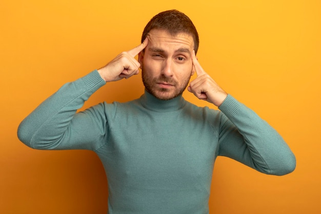 Thoughtful young man looking at front doing think gesture isolated on orange wall