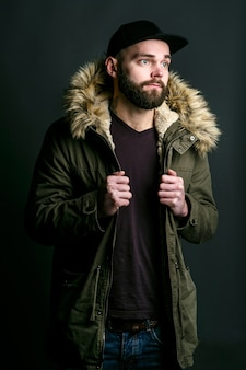 Thoughtful young man in parka with fur hood