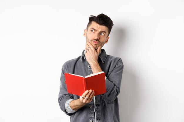 사려 깊은 젊은 남자는 그의 일정을 계획, 옆으로 잠겨있는 찾고, 열린 된 플래너 또는 저널, 흰색 배경에 서 들고.