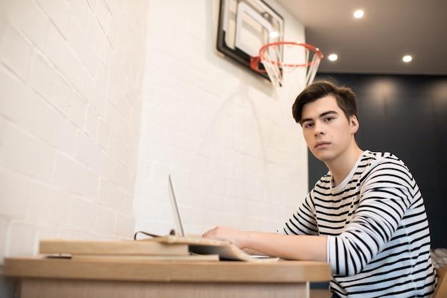 Вдумчивый молодой человек, сидя у себя дома с помощью ноутбука