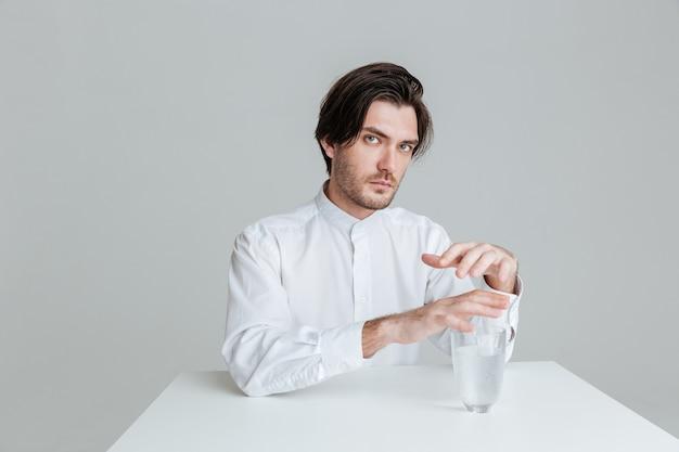회색 벽에 물 유리가 분리된 탁자에 앉아 있는 사려 깊은 청년