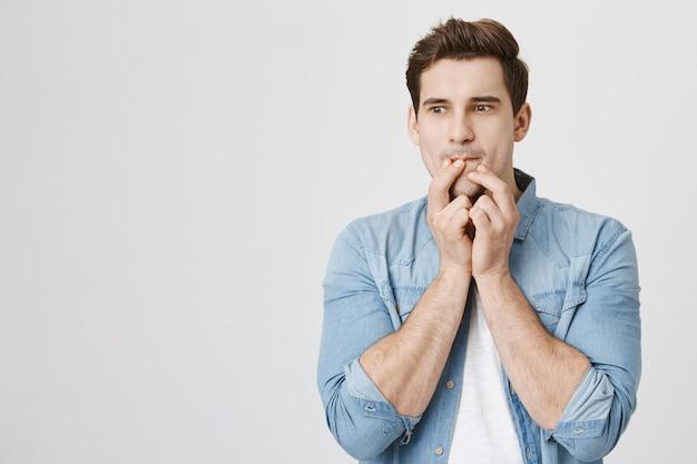 思いやりのある若い男が唇に触れて目をそらす、アイデアを持っている