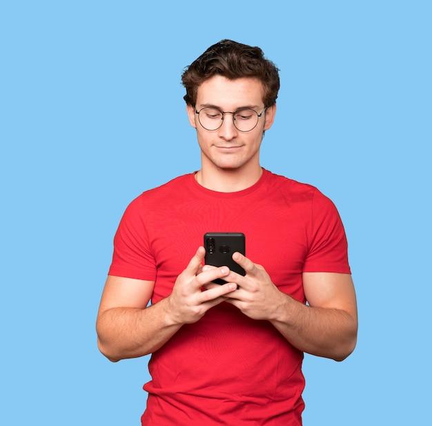 Вдумчивый молодой человек с помощью своего мобильного телефона