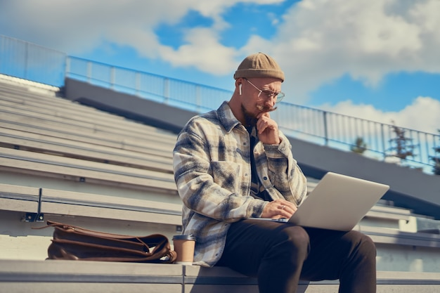 노트북 프리랜서를 사용하여 키보드로 온라인 야외 타이핑 작업을 하는 사려 깊은 청년