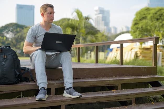 공원에서 나무 다리에 노트북을 사용하는 사려 깊은 젊은 남자