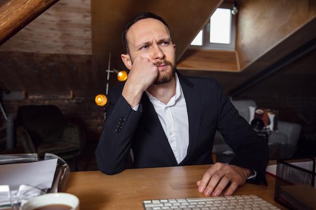 Вдумчивый. молодой человек, работающий в режиме видеоконференции с коллегами в офисе. интернет-бизнес, образование во время коронавируса и карантина. работа, финансы, современные технические концепции. вид с экрана.