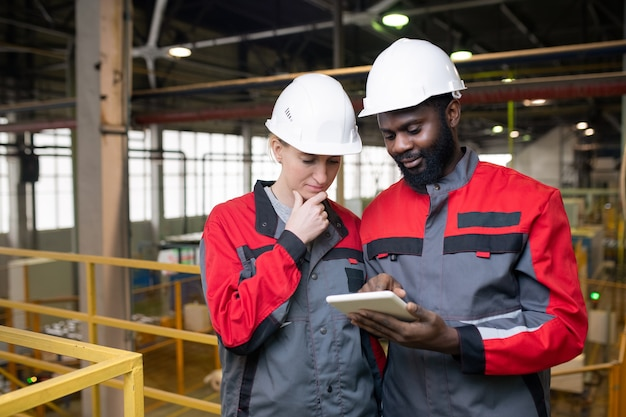 Thoughtful young multi-ethnic workers in helmets using tablet while analyzing industrial production data
