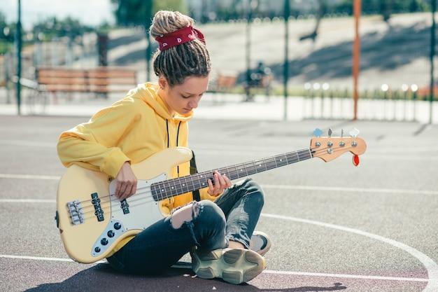 スポーツグラウンドでギターを弾きながら集中しているように見えるドレッドヘアを持つ思いやりのある若いミュージシャン