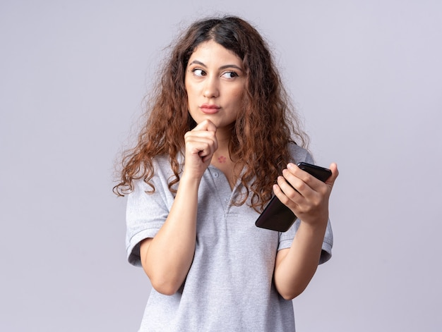Thoughtful young pretty caucasian girl holding mobile phone keeping hand on chin looking at side