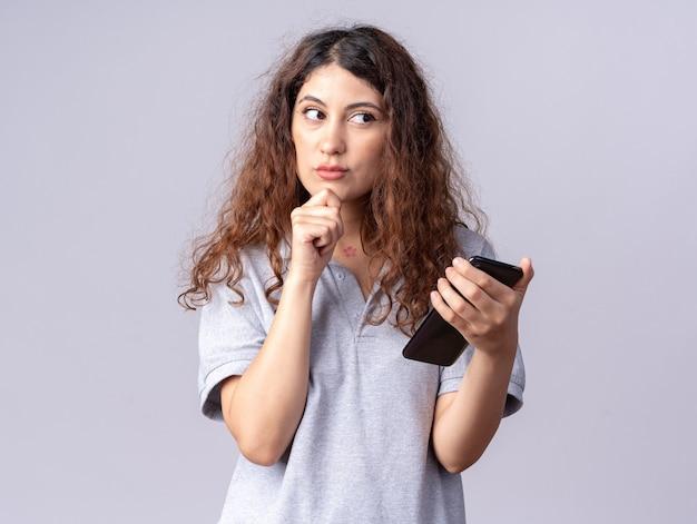 思いやりのある若いかなり白人の女の子が携帯電話を持ってあごに手を置いて横を見て
