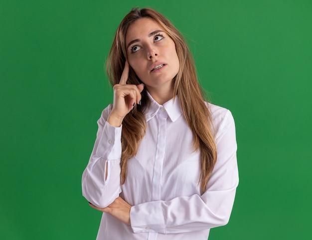 La giovane ragazza abbastanza caucasica premurosa mette il dito sul tempio e guarda a lato sul verde