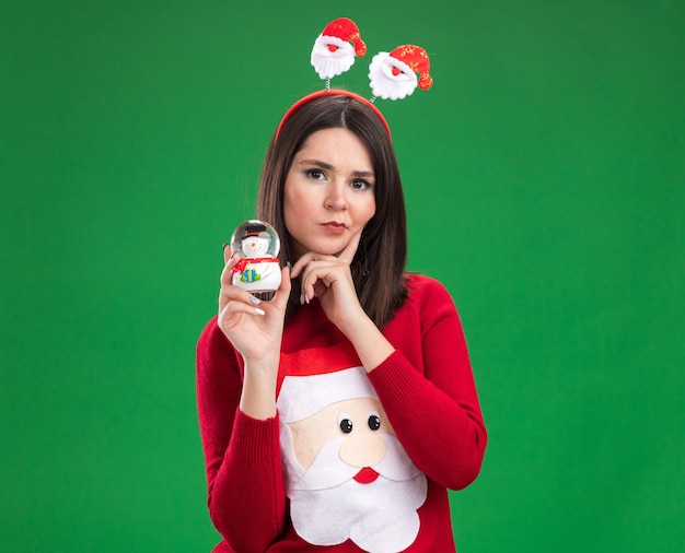 Thoughtful young pretty caucasian girl wearing santa claus sweater and headband holding snowman figurine  keeping hand on chin isolated on green wall with copy space