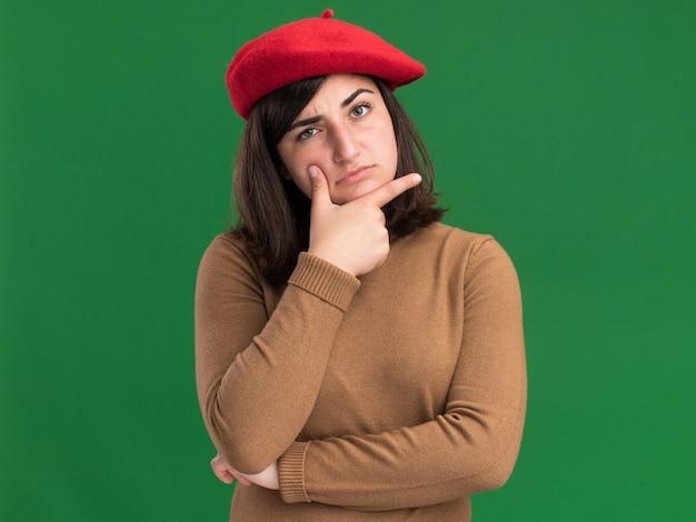 あごを保持し、緑のカメラを見ているベレー帽の帽子を持つ思いやりのある若いかなり白人の女の子