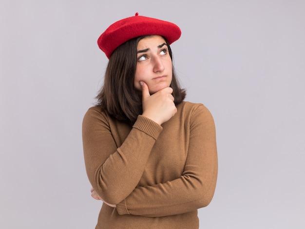あごを保持し、コピースペースで白い壁に孤立して見上げるベレー帽の帽子を持つ思いやりのある若いかなり白人の女の子