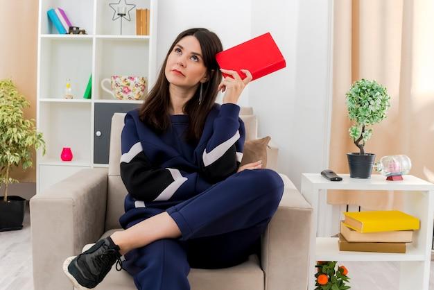 사려 깊은 젊은 예쁜 백인 여자는 다른 하나를 찾고 다리를 넣어 책을 들고 설계 된 거실에서 안락의 자에 앉아