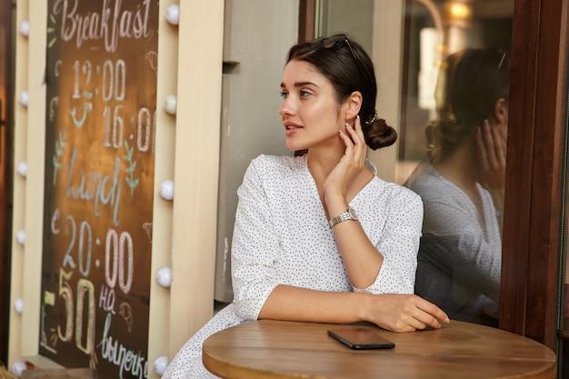 Задумчивая молодая симпатичная темноволосая женщина с прической в виде пучка строго смотрит в сторону и касается шеи поднятой рукой, сидя за столом над летней террасой