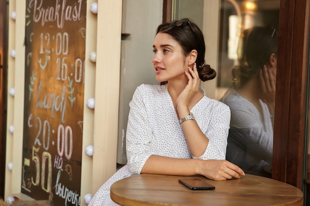 Thoughtful young pretty dark haired female with bun hairstyle looking aside severely and touching her neck with raised hand, sitting at table over summer terrace
