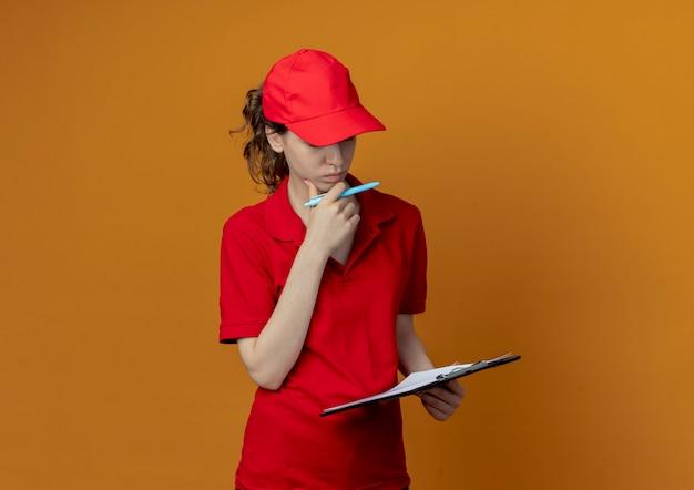 Задумчивая молодая красивая девушка доставки в красной форме и кепке трогательно подбородок держит буфер обмена и ручку, глядя в буфер обмена, изолированные на оранжевом фоне с копией пространства