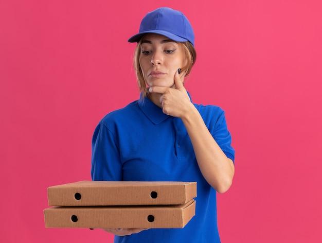 Premurosa giovane bella ragazza di consegna in uniforme mette la mano sul mento e guarda le scatole per pizza sul rosa