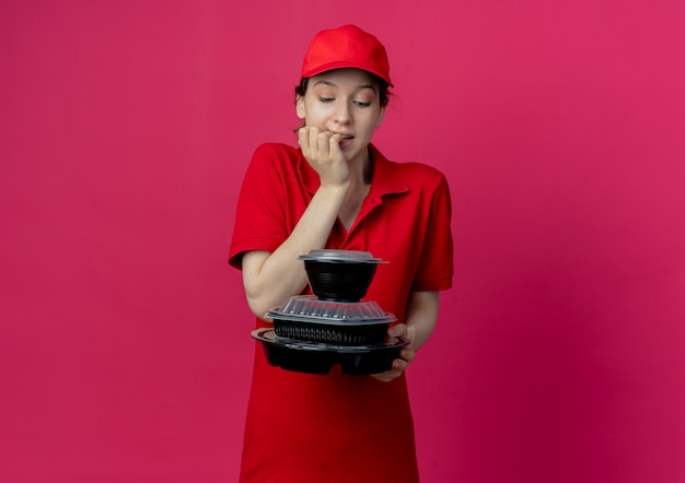 Thoughtful young pretty delivery girl wearing red uniform and cap holding and looking at food containers and biting fingers isolated on crimson background with copy space