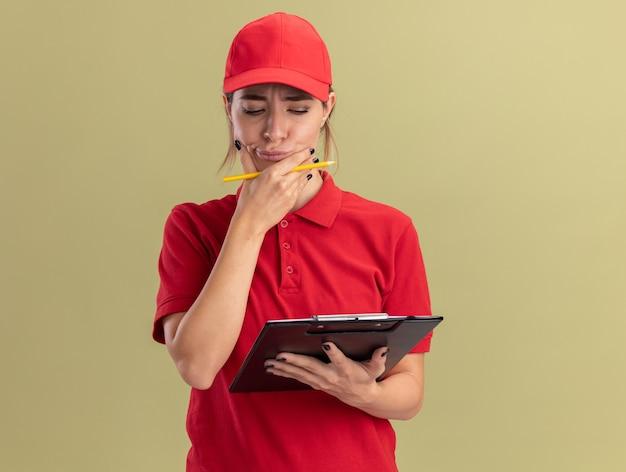 Задумчивая молодая симпатичная курьерская женщина в униформе кладет руку на подбородок, держа карандаш, и смотрит в буфер обмена, изолированный на оливково-зеленой стене
