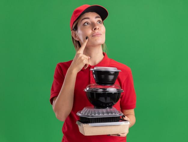 La giovane donna graziosa premurosa di consegna in uniforme tiene i contenitori di cibo sul pacchetto dell'alimento che osserva in su isolato sulla parete verde