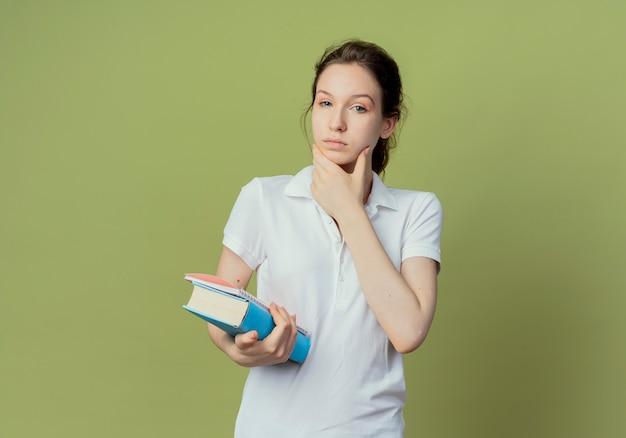 本とメモ帳を持って、顔に触れる思いやりのある若いきれいな女子学生