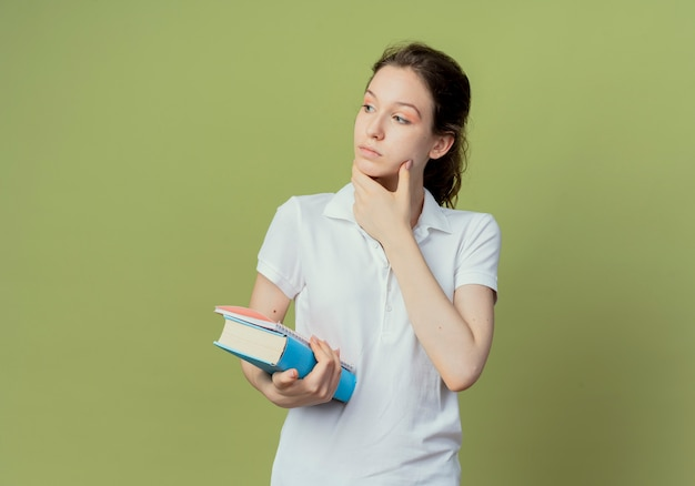 Thoughtful young pretty female student holding book and note pad looking at side and touching face isolated on olive green background with copy space