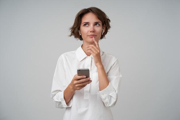 Задумчивая молодая симпатичная женщина с повседневной прической смотрит вверх и держит указательный палец на нижней губе, позирует со смартфоном в руке