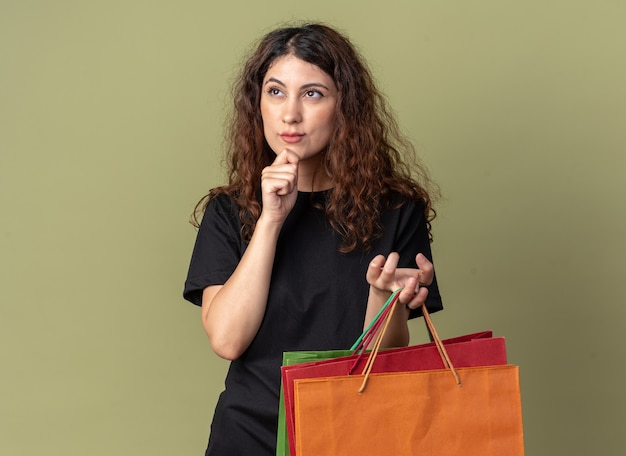 Thoughtful young pretty girl holding shopping bags keeping hand on chin looking up