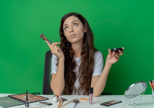 緑の背景で隔離の赤面と化粧ブラシを保持している化粧ツールと化粧テーブルに座っている思いやりのある若いかわいい女の子