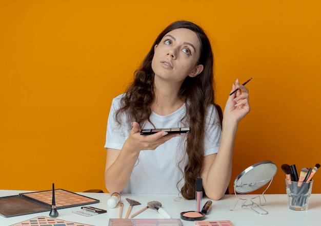 Задумчивая молодая красивая девушка сидит за столом для макияжа с инструментами для макияжа, держа палитру теней и кисть, глядя вверх