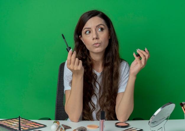 녹색 배경에 고립 된 측면을보고 마스카라를 들고 메이크업 도구와 메이크업 테이블에 앉아 사려 깊은 젊은 예쁜 여자