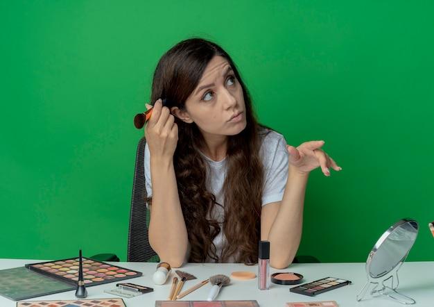 Задумчивая молодая красивая девушка сидит за косметическим столом с инструментами для макияжа, касаясь головы кистью для румян, глядя в сторону и держа руку в воздухе, изолированную на зеленом фоне