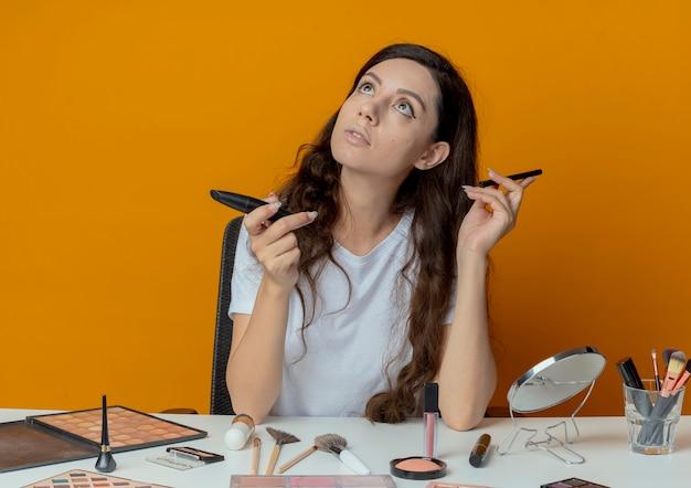 Riflessivo giovane bella ragazza seduta al tavolo per il trucco con strumenti di trucco tenendo eyeliner e mascara cercando isolato su sfondo arancione