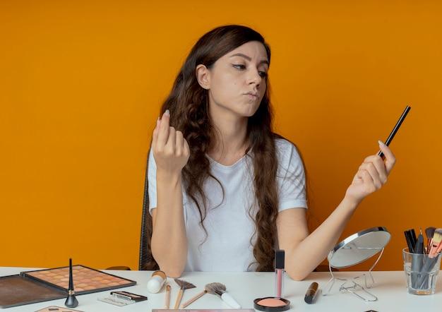 Riflessivo giovane bella ragazza seduta al tavolo per il trucco con strumenti di trucco tenendo e guardando eyeliner tenendo la mano in aria isolata su sfondo arancione