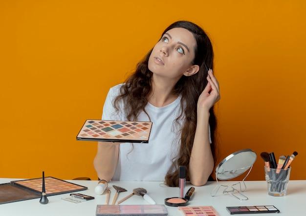 Giovane bella ragazza premurosa che si siede al tavolo di trucco con strumenti di trucco che osserva in su che tiene la tavolozza dell'ombretto e che tocca la testa con la spazzola dell'ombretto isolata su fondo arancio