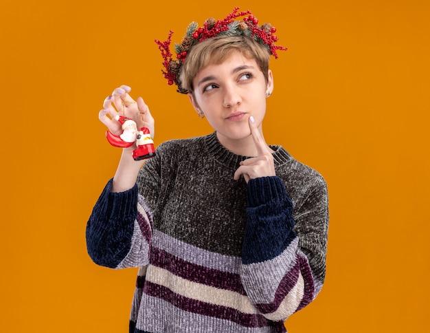 Riflessivo giovane bella ragazza che indossa la corona di testa di natale che tiene babbo natale ornamenti natalizi guardando il mento toccante lato isolato su sfondo arancione